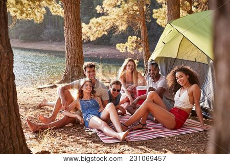 Friends camping out by a lake smiling to camera