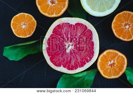 Mixed Citrus Background. Assorted Fresh Citrus Fruits With Leaves On Black Stone Table. Lemon, Grape