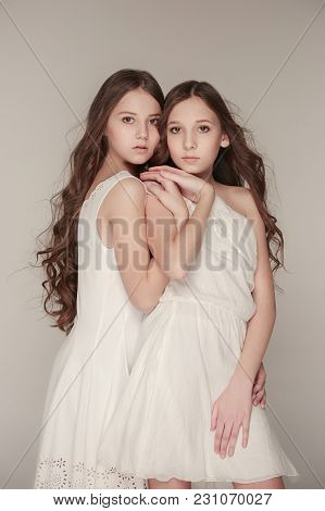 The Group Of Girls Standing Together And Posing At Camera. Studio Portrait Of Young Attractive Fashi