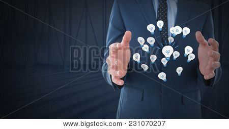 Digital composite of Idea light bulb app icons and Businessman with hands palm open and dark background