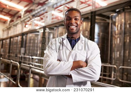 Young black male wine factory technician smiling to camera