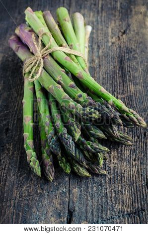 Bunch Of Fresh Green Asparagus Tied With Twine On An Old Wooden Background. Healthy Food Concept.