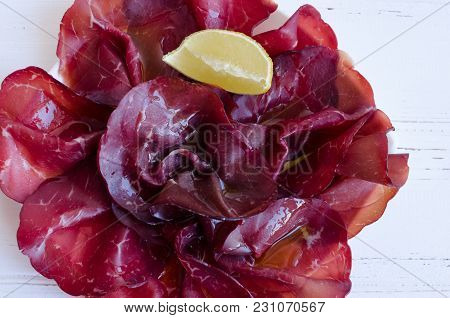 Slices Of Italian Meat Bresaola Served With Olive Oil And Lemon On A Plate On White Background. Trad