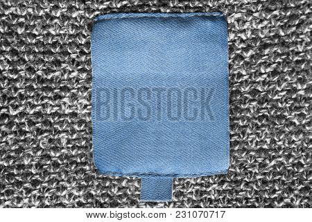 Blank Blue Textile Clothes Label On Grey Knitted Background