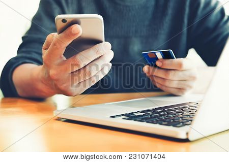 Online Payment And Shopping, Young Man Holding Smartphone And Creditcard And Using Computer Laptop F