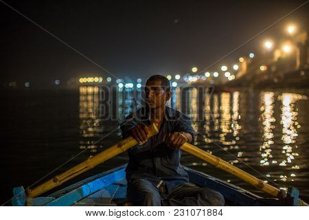 VARANASI, INDIA - MAR 13, 2018: Boatmen on the Ganga river at night. Varanasi is one of the most important pilgrimage sites in India and is one of the 7 sacred cities of Hinduism.