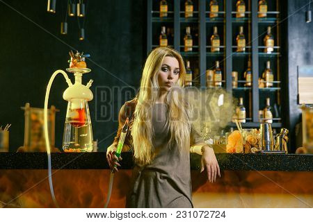 Young Blonde Woman Smoking A Hookah Behind The Bar. Cloud Of Smoke. Beauty Portrait Of Young Woman E
