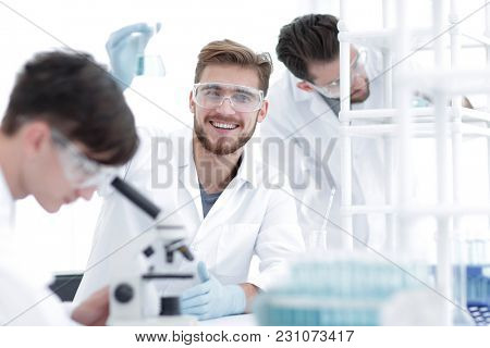 male biologist on blurred background colleagues.