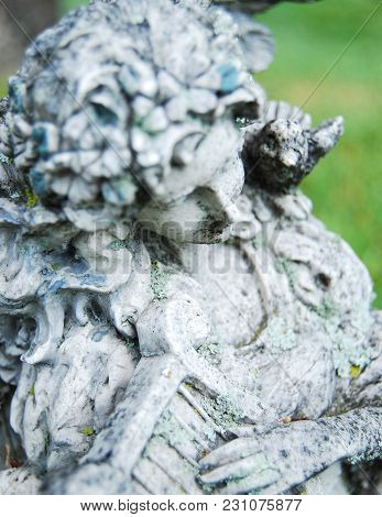 This Is An Old Statue Withered With Time Of An Angel Playing A Harp.