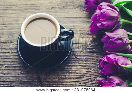 Cup Of Coffee With Bouquet Of Purple Tulips
