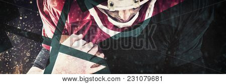 American football player protecting football against grey background