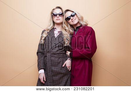 fashion portrait of two girls, best friends posing indoor on beige background wearing winter stylish coat.