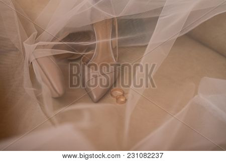 Beige Bridal Stylish Shoes And A Golden Rings Are Covered With A Veil. Wedding Details.