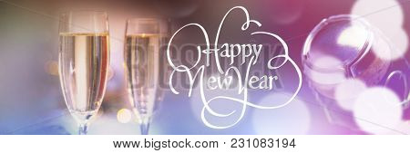Happy new year against champagne flutes on table
