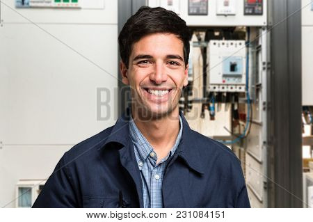 Smiling electrician in front of an electrical panel