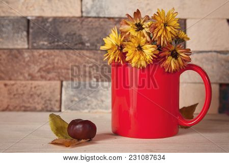 Yellow Flowers In Red Cup On The Kitchen Table. Still Life