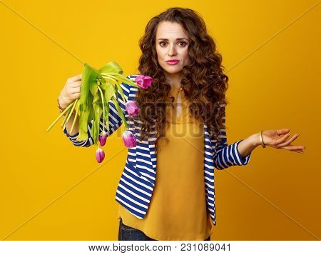 sad young woman in striped jacket on yellow background holding wilted flowers poster