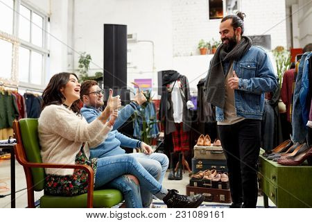 sale, shopping, fashion and people concept - friends choosing clothes at vintage clothing store and showing thumbs up