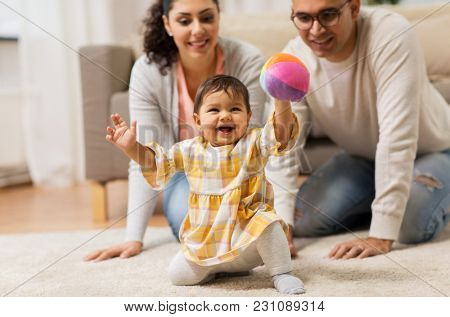 family, parenthood and people concept - happy mother, father and baby daugter playing with ball at home