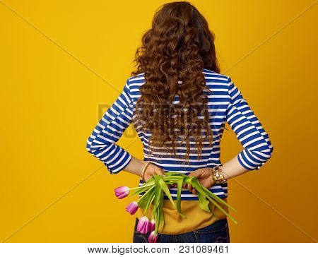 Trendy Woman Against Yellow Background Holding Wilted Flowers
