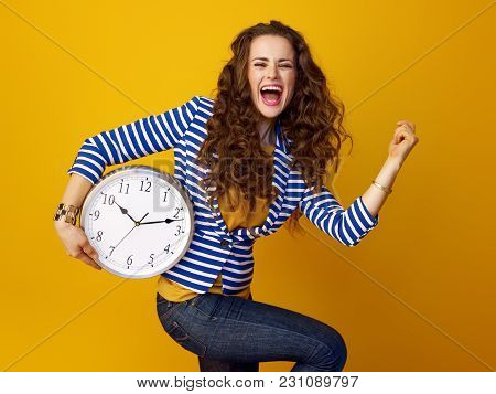 Cheerful Woman On Yellow Background With Clock Rejoicing
