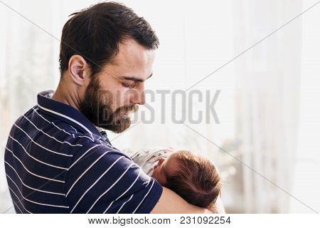 Happy Father Holds His Newborn Sleeping Baby At Home.