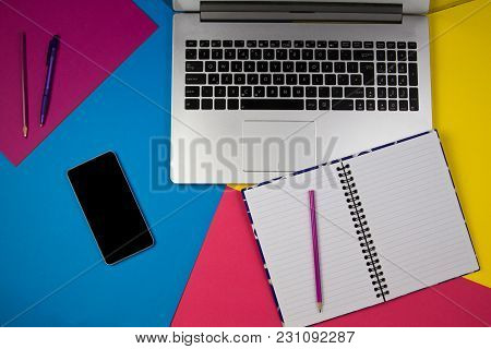 Laptop Computer, Open Notebook And Mobile Phone On Colorful Background