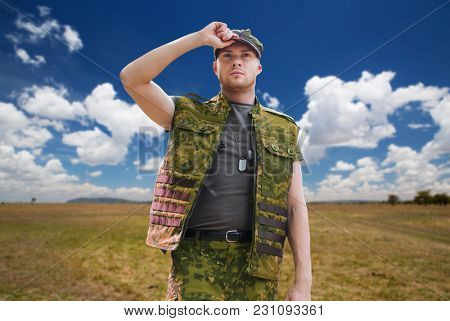 army, national service and people concept - young soldier or ranger wearing military uniform over natural background and blue sky