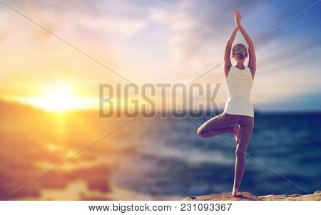 fitness, yoga and people concept - happy woman making tree pose and meditating outdoors over sea background