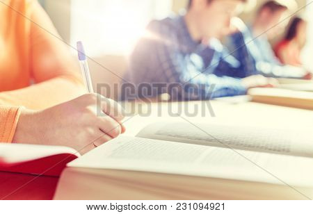 education, learning and people concept - close up of student girl hand with book writing school test