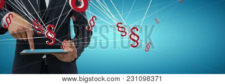 Mid section of businessman using digital tablet against abstract blue background
