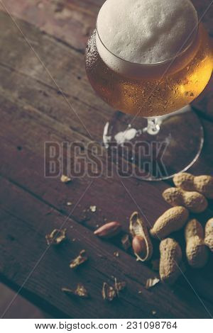Glass Of Cold Pale Beer And Some Peanuts On A Rustic Wooden Table. Selective Focus On The Foam