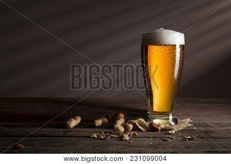 Glass Of Cold Light Beer Placed On A Burlap Coaster And Some Peanuts On A Rustic Wooden Table
