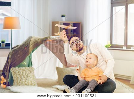 family, childhood, fatherhood and people concept - happy father and little son playing with toy airplane at home over kids room and tepee background