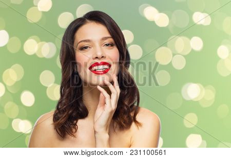 beauty, make up and people concept - happy smiling young woman with red lipstick posing over summer green lights background