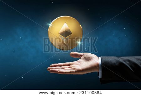 cryptocurrency, financial technology and business concept - businessman hand with golden ether coin over space background