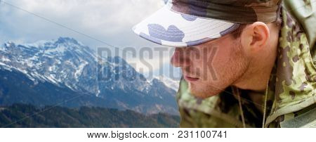army, national service and people concept - close up of young soldier in military uniform over mountains background