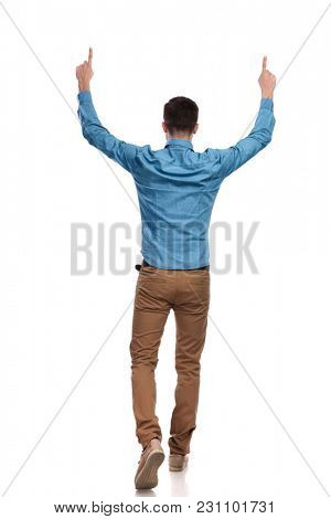 back view of a casual man walking and pointing up with hands in the air on white background