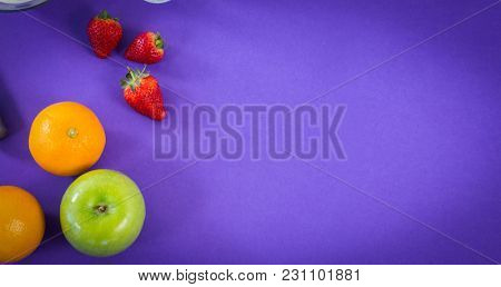 Overhead ciew of various fruits on purple background