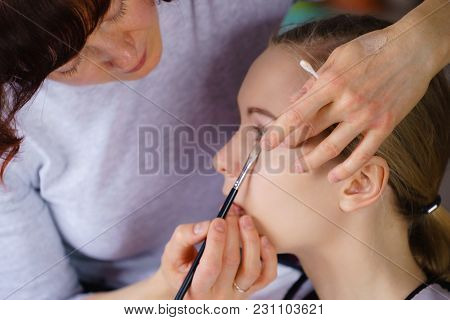 Visage Concept. Close Up Woman Getting Make Up On Eyelids. Applying Eyeshadow With Brush By Professi