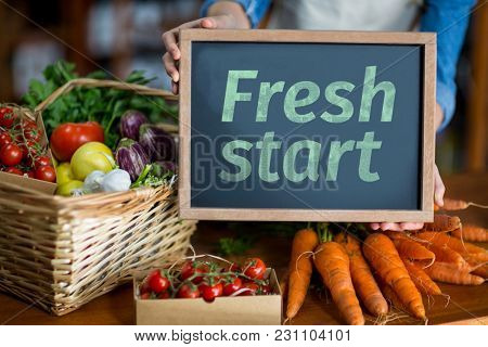 Fresh start against woman holding board in front of vegetables