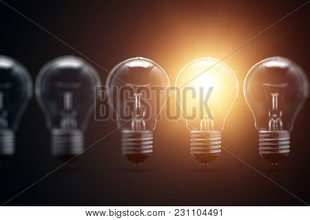 A Series Of Electric Light Bulbs, Only One Glows, Against A Dark Background. The Concept Of Several