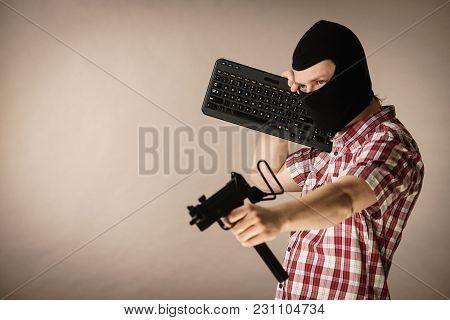 Crazy Hacker Man. Unrecognizable Guy Wearing Black Balaclava Holding Computer Keyboard And Gun. Hate