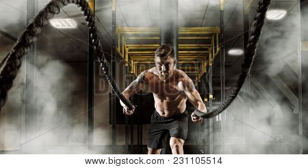 Man working out with battle ropes at gym