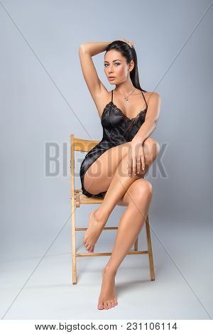 Beautiful Brunette Woman In Black Lingerie Posing With The Chair - Fashion Portrait On The Grey Back