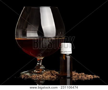 Glass With Alcohol, Liquid For Smoking And Scattered Tobacco Isolated On Black Background