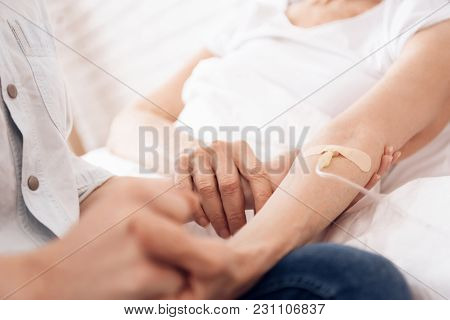 Girl Is Nursing Elderly Woman In Bed At Home. They Are Holding Hands. Woman Is Connected To Drop Cou