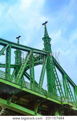 Closeup On Liberty Bridge Or Szabadsag Green Metal Structure With Coat Of Arms In Budapest, Hungary