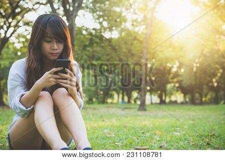Cute Asian Woman Reading Pleasant Text Message On Mobile Phone While Sitting In Park Spring Day. Asi