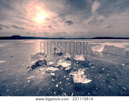 Winter View Of The Frozen  Sea To The Opposite Bank.  The Sun In Ice Colorful Glare
